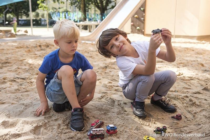 zwei Jungen spielen im Sand