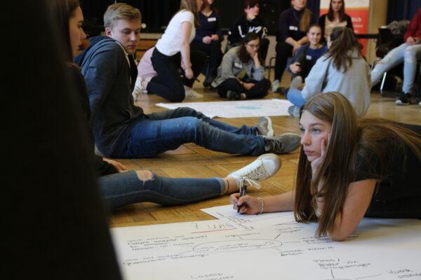 Jugendliche zeichnen auf dem Boden ein Plakat