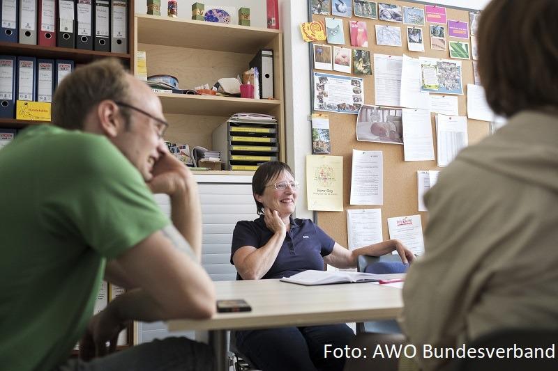 Eine Frau berät mehrere Personen in einem Büro und lacht
