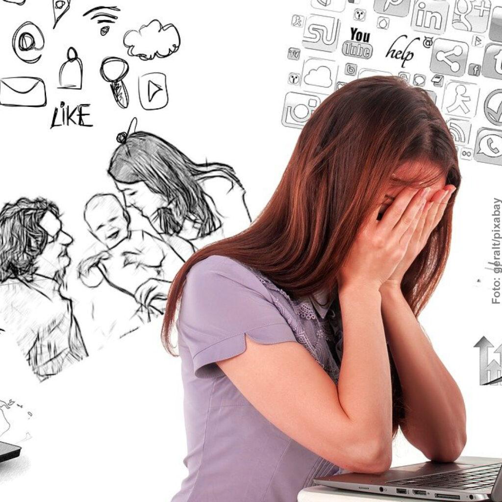 Eine Frau sitzt vor dem Laptop und schlägt die Hände vor dem Gesicht zusammen
