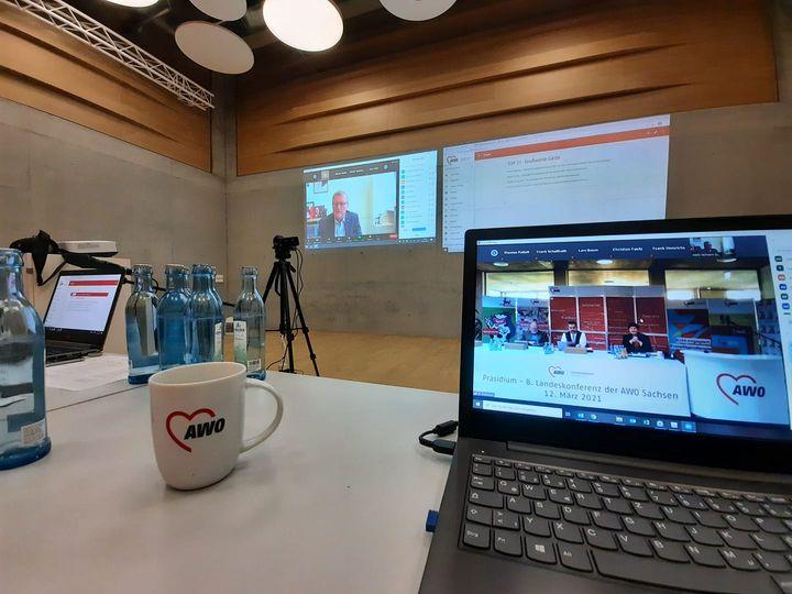 Ein Ausschnitt von der Zoom Konferenz im Laptop, dahinter die Leinwand