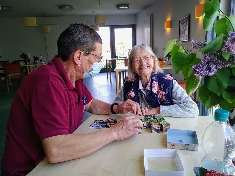 Zwei ältere Menschen plaudern fröhlich am Tisch
