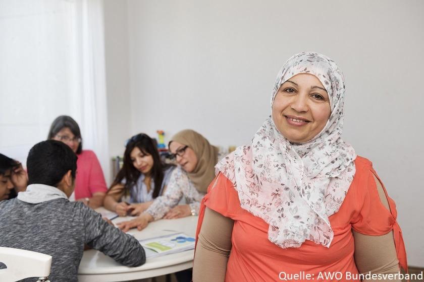 Eine Lächelnde Frau im Vordergrund und fünf Personen dahinter an einem Tisch im Gespräch