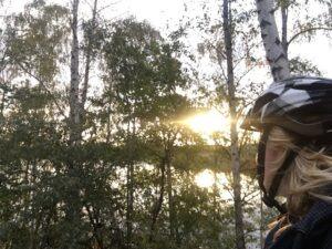 Eine Frau mit Helm schaut in die Sonne, die durch die Bäume scheint