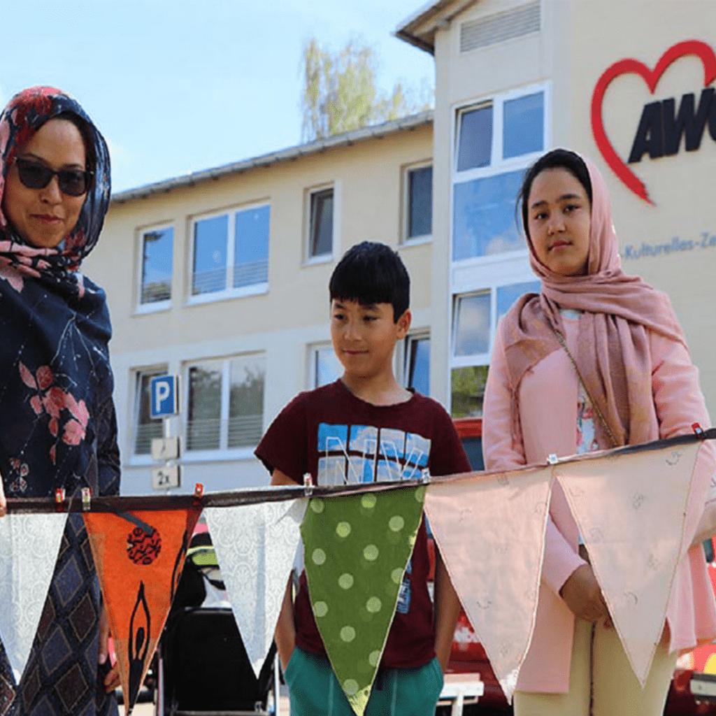Drei Migrant*innen vor einem interkulturellen Zentrum der AWO