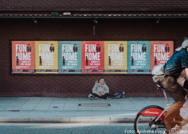 Ein obdachloser Mann, der auf dem Bürgersteig sitzt. hinter einer Wand mit aufgeklebten Plakaten