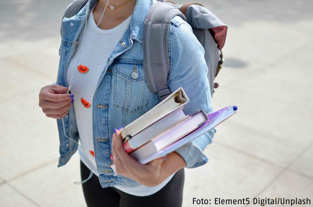 Eine Frau, die einen Rucksack trägt, hält mehrere Bücher in ihren Armen