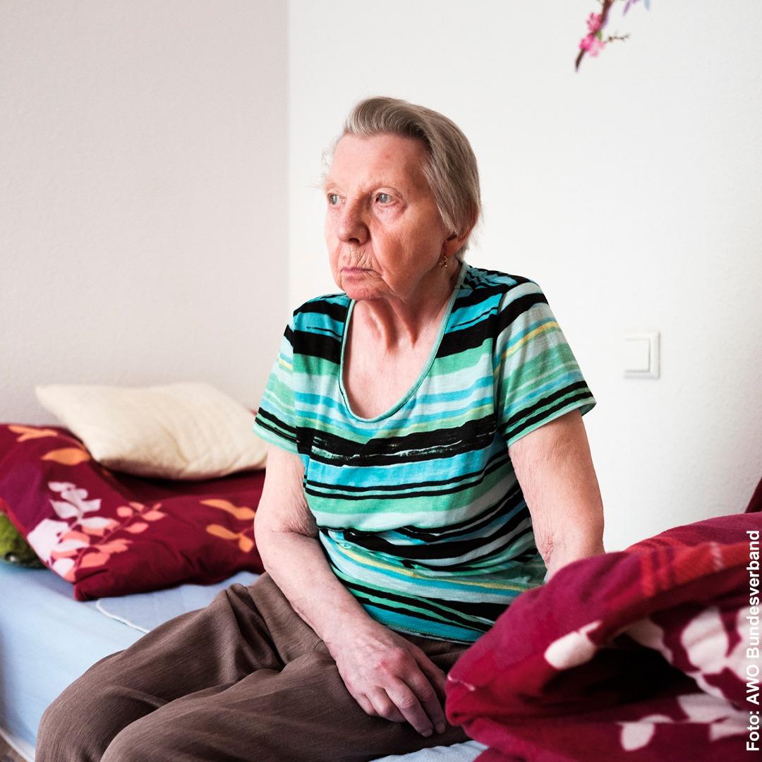 Eine alte Frau sitzt auf dem Bett und starrt vor sich hin