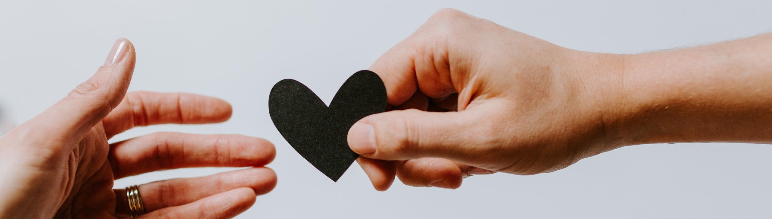 Ein Papierherz wird von einer Hand zur anderen gereicht