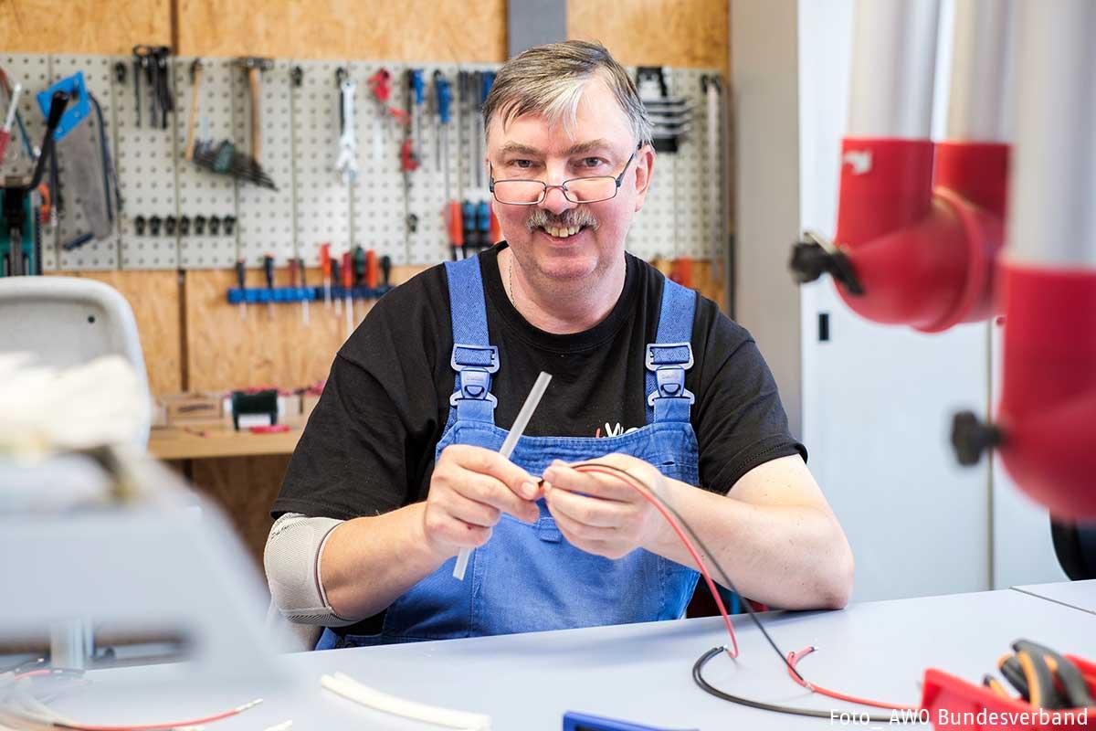 Ein Mann sitzt in einer Werkstatt, arbeitet mit Kabeln und lächelt in die Kamera