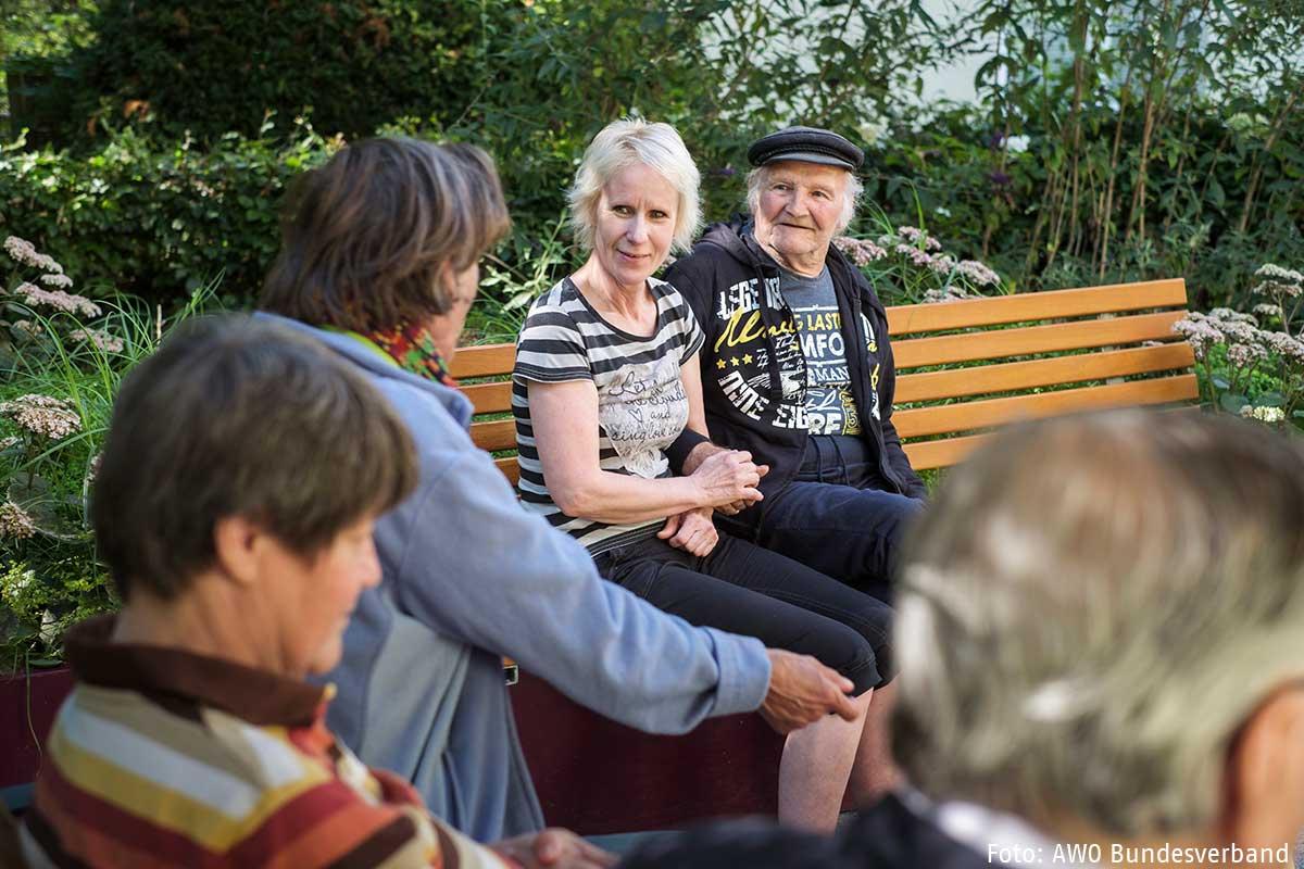 Mehrere alte Menschen Senioren und Seniorinnen sitzen draußen auf Bänken und sprechen miteinander und einer Pflegekraft