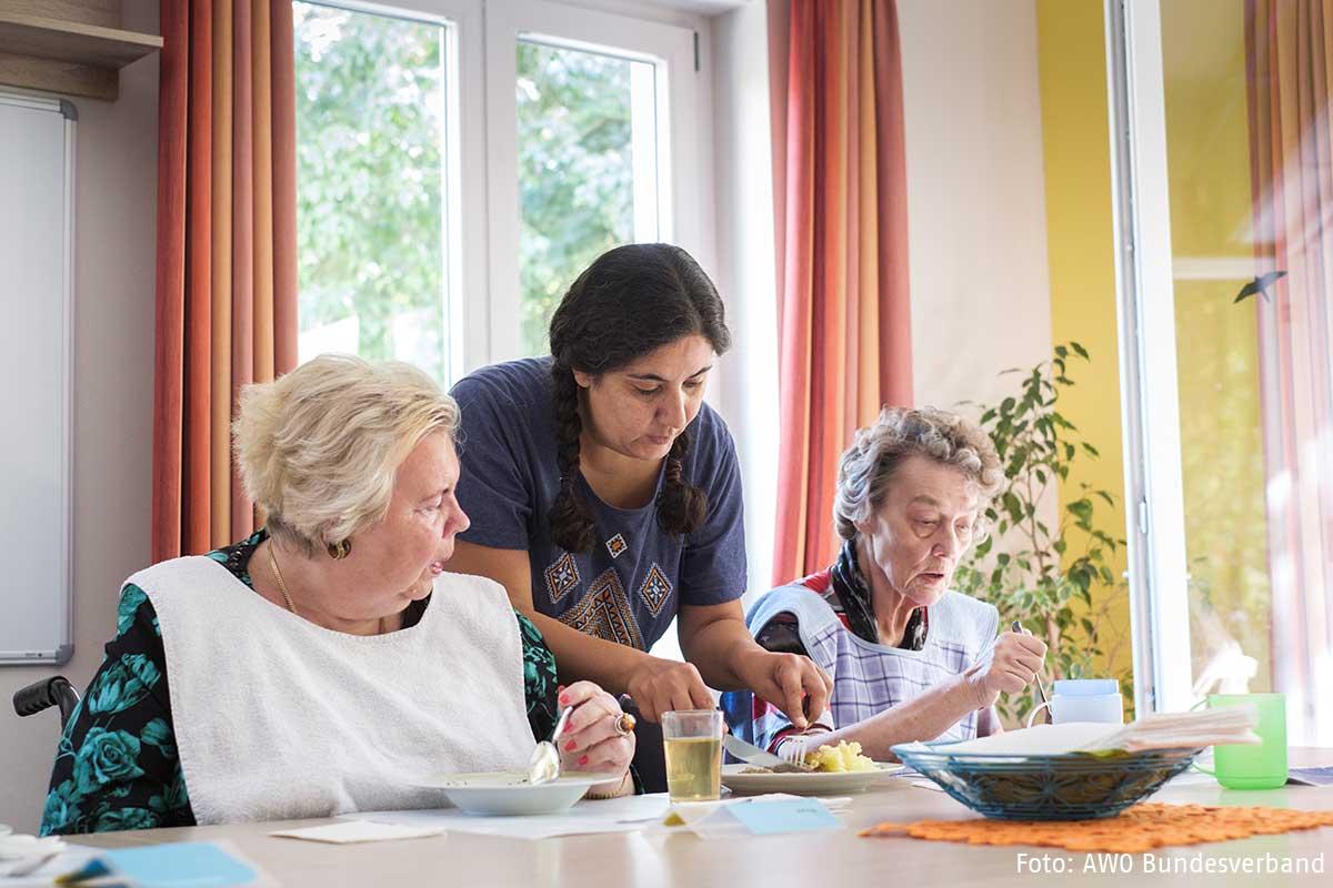 Eine Frau hilft zwei alten Frauen Seniorinnen beim Essen
