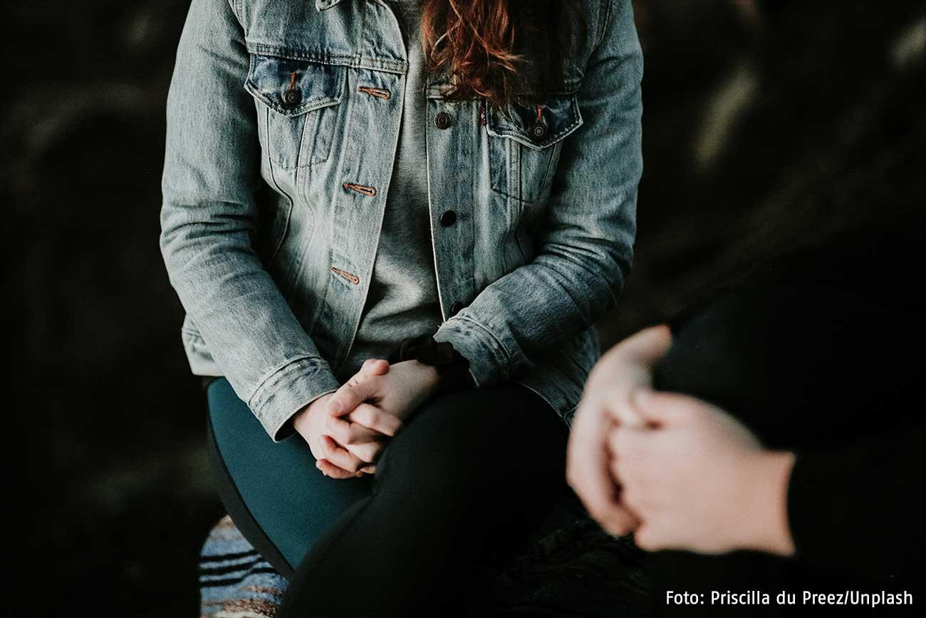 Eine Frau sitzt mit zusammengelegten Händen