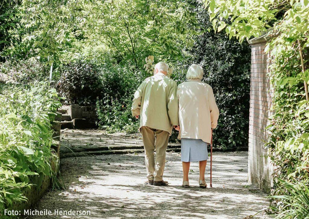 Zwei ältere Menschen, die auf einem grünen Weg spazieren gehen