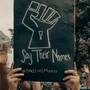 Zwei Hände halten ein Schild hoch, auf dem steht:
