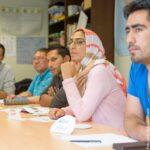 Vier Männer und eine Frau mit Kopftuch sitzen in einem Klassenzimmer und hören zu