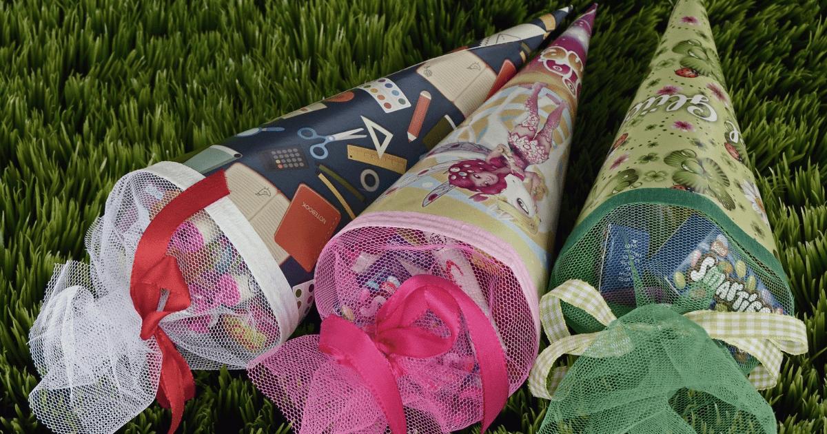3 Zuckertüten liegen nebeneinander auf dem Gras
