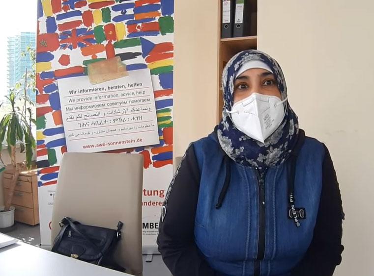 Eine Frau, die eine Maske und eine blaue Jacke trägt, gibt ein Interview