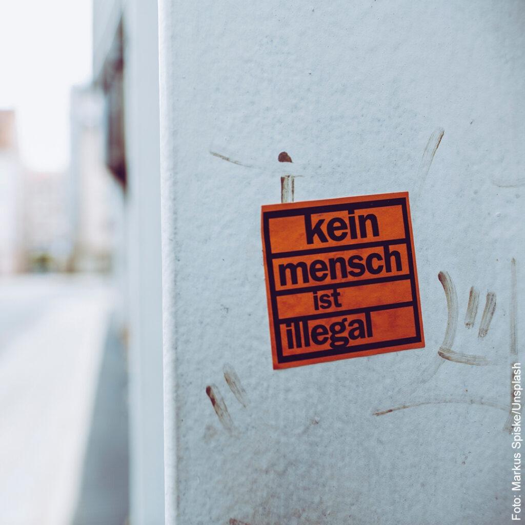 """An einer Mauer klebt ein Aufkleber: """"Kein Mensch ist illegal"""""""