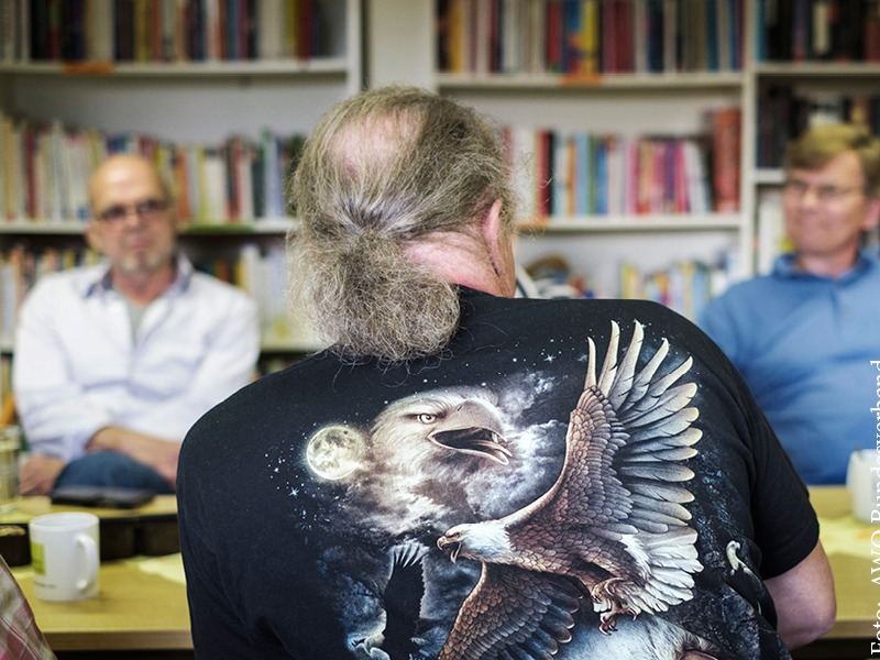 Ein Mann sitzt an einem Tisch zwei Männern gegenüber in einem Gespräch Beratung