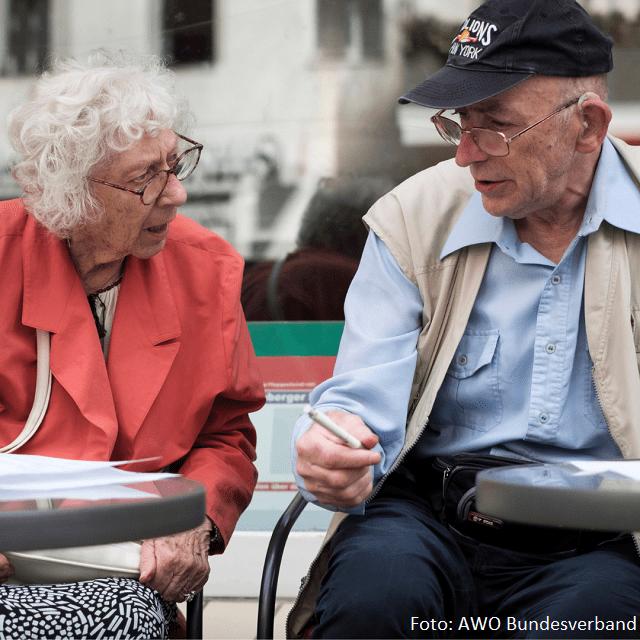Ein alter Mann und eine alte Frau sitzen am Tisch und unterhalten sich