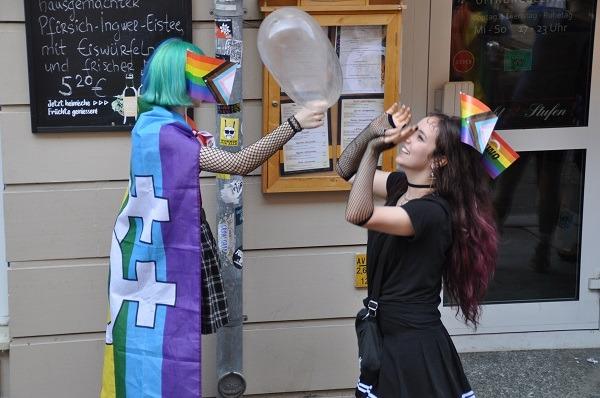Zwei Besucher*innen genießen den CSD mit einem Riesenluftballon