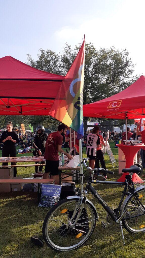 Ein Fahrrad mit AWO Regenbogenfahne vor dem AWO Stand