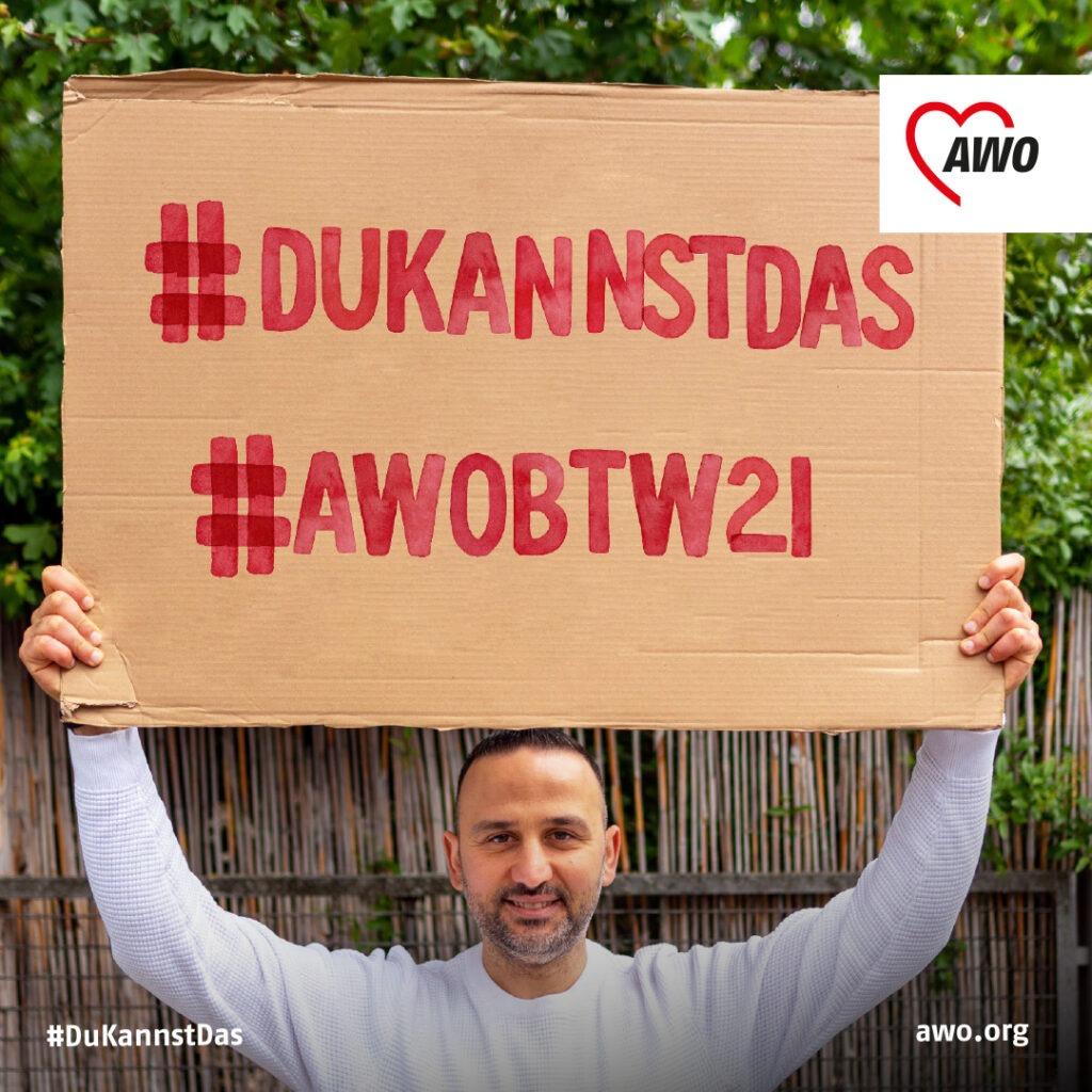 Ein Mann hält ein Plakat hoch mit den Hashtags #DuKannstDas und #AWOBTW21