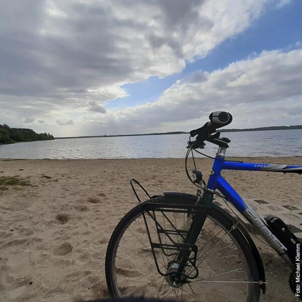 Fahrrad vor See auf Sandstrand