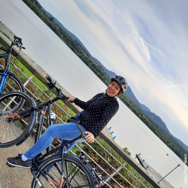 Frau auf Fahrrad vor See