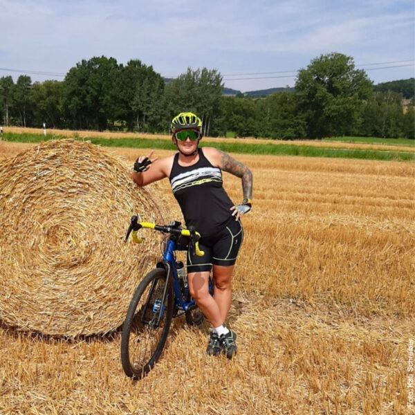 Frau mit Fahrrad an Heuballen gelehnt