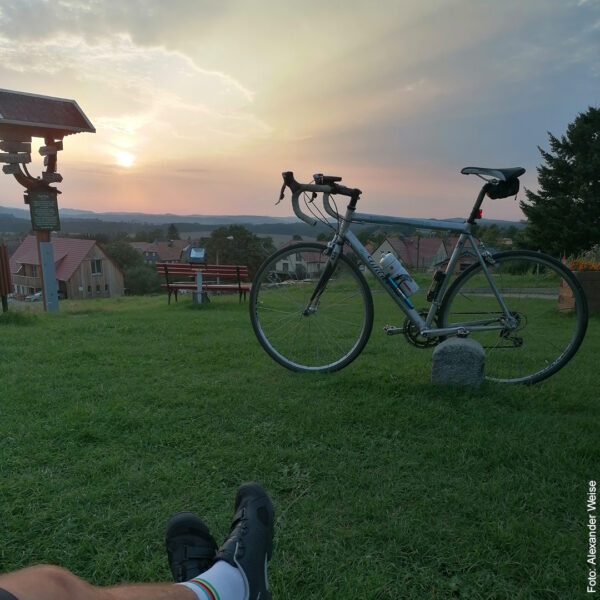 Fahrrad vor Dorfkulisse mit Sonnenuntergang