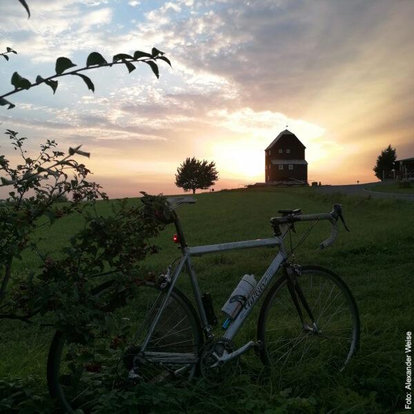 Fahrrad vor schönem Haus bei Sonnenuntergang
