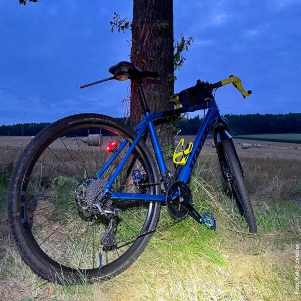 Fahrrad im Dunkeln vor Baum