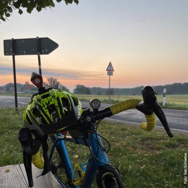 Fahrrad vor Straße bei Sonnenaufgang