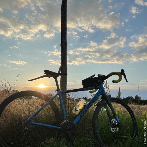 Fahrrad auf Feld vor blauem Himmel mit Wolken