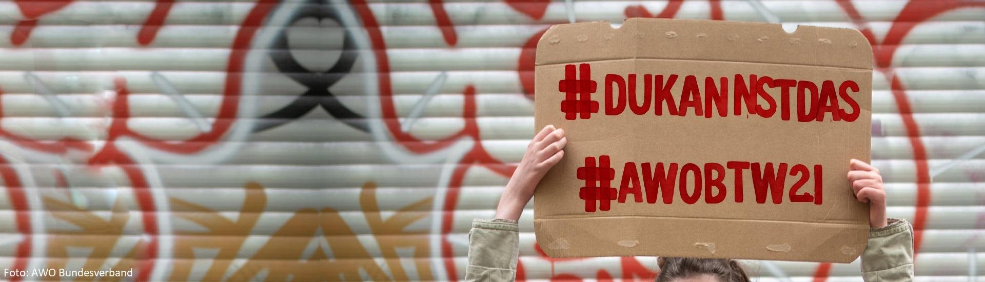 Jemand hält ein Pappschild mit den Hashtags #DuKannstDas und #AWOBTW21 hoch