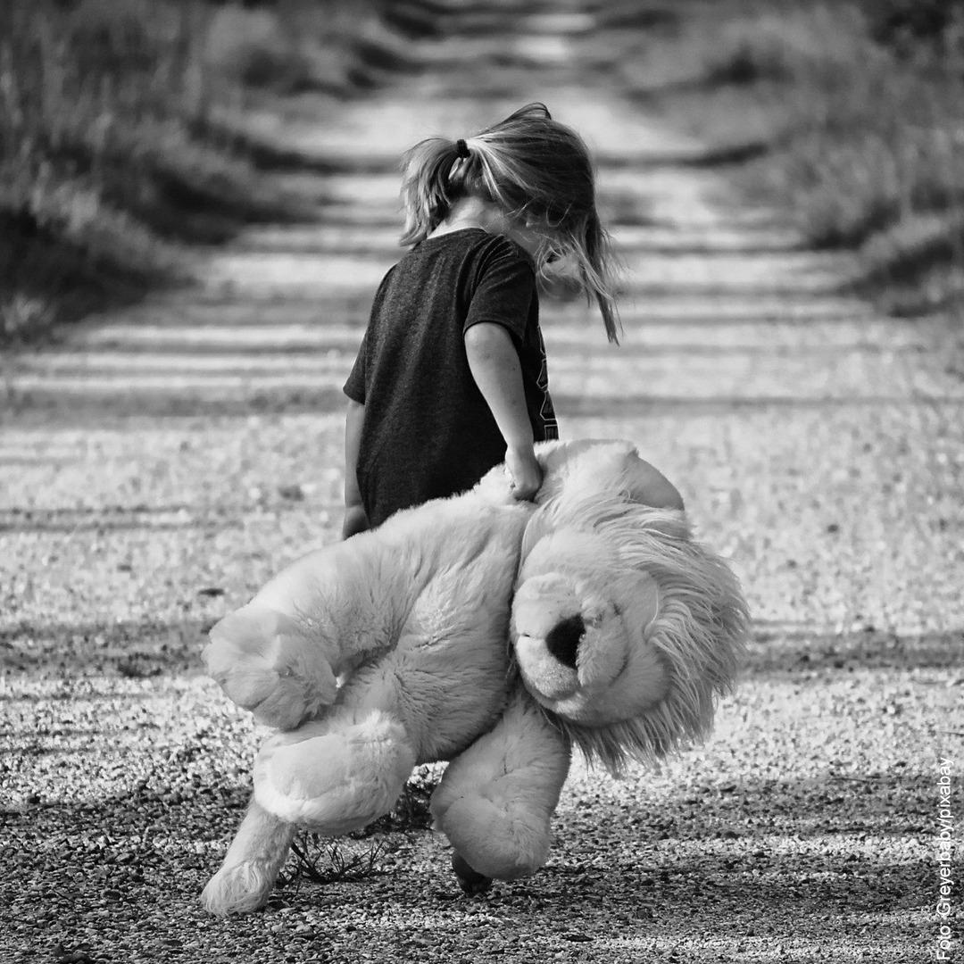 Ein Mädchen schleppt ein Riesenkuschletier über eine steinige Straße