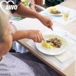 Eine alte Frau bekommt ihr Mittagessen geschnitten