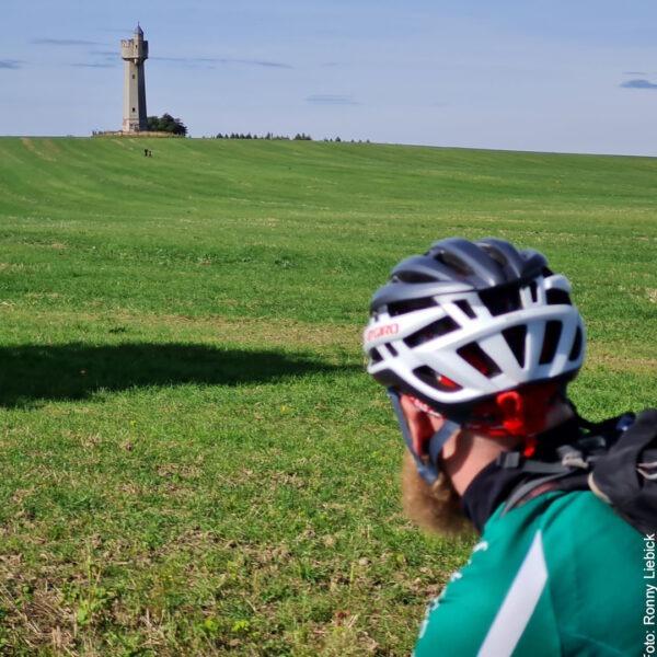 Fahrradfahrer schaut auf Leuchtturm