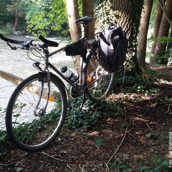 Fahrrad parkt am Bach in der Sonne