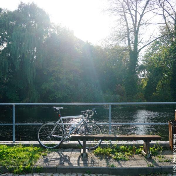 Fahhrad parkt in der Sonne am Fluss
