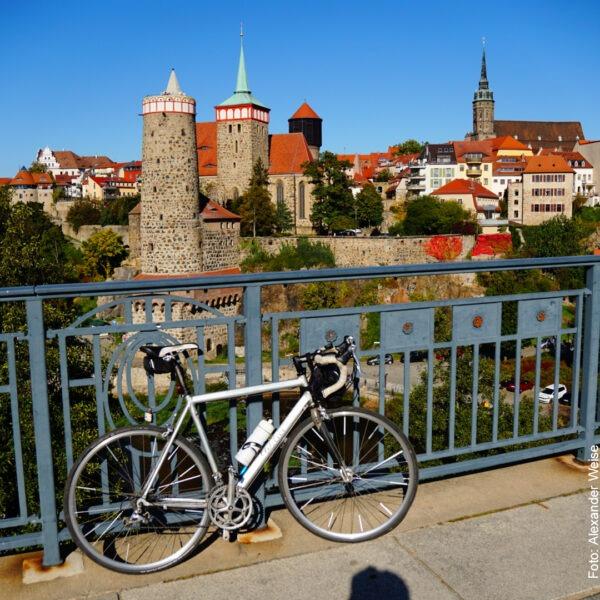 Fahhrad steht an der Brücke, im Hintergrund die Altstadt Bautzens