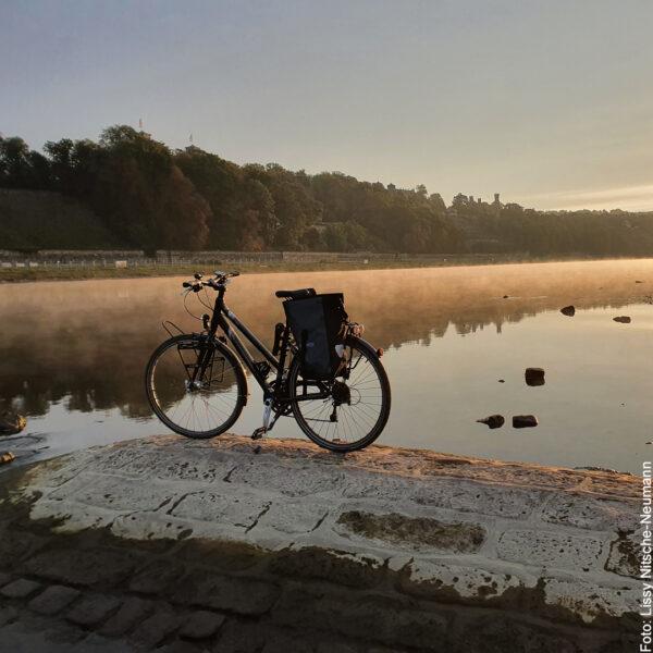 Die elbe spiegelt die Landschaft in der Morgensonne, Fahrrad davor